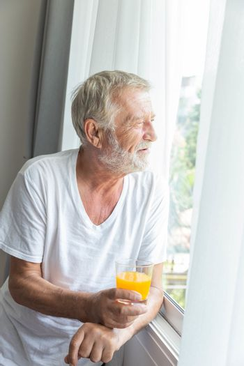 Senior retirement man stand beside room window holding a glass of orange juice look outside with happiness