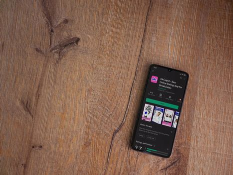 Lod, Israel - July 8, 2020: OkCupid app play store page on the display of a black mobile smartphone on wooden background. Top view flat lay with copy space.