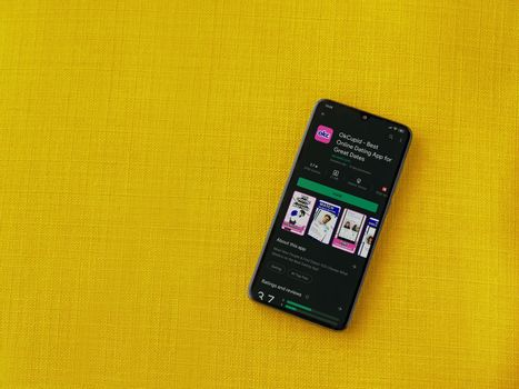 Lod, Israel - July 8, 2020: OkCupid app play store page on the display of a black mobile smartphone on a yellow fabric background. Top view flat lay with copy space.