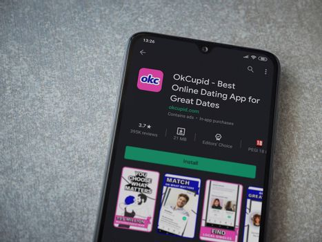 Lod, Israel - July 8, 2020: OkCupid app play store page on the display of a black mobile smartphone on ceramic stone background. Top view flat lay with copy space.