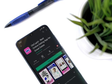 Lod, Israel - July 8, 2020: Modern minimalist office workspace with black mobile smartphone with OkCupid app play store page on a white background. Close up top view flat lay.