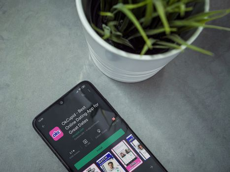 Lod, Israel - July 8, 2020: Modern minimalist office workspace with black mobile smartphone with OkCupid app play store page on a marble background. Close up top view flat lay.
