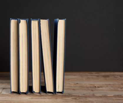 stack of various hardback books on the background of an empty black chalk board, back to school, copy space