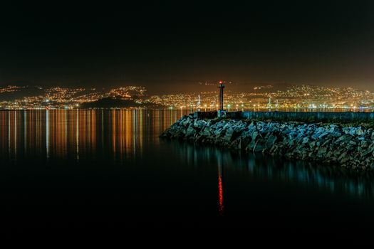 An horizontal colorful shot of the lighthouse during the night with the city skyline during as the background