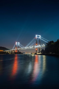 A luminous bridge reflecting in the water at night