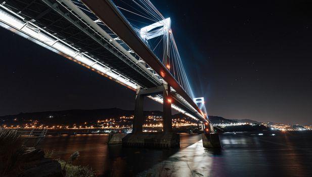 Luminous bridge from below reflecting in the water at night