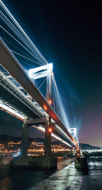 A luminous bridge from below reflecting in the water