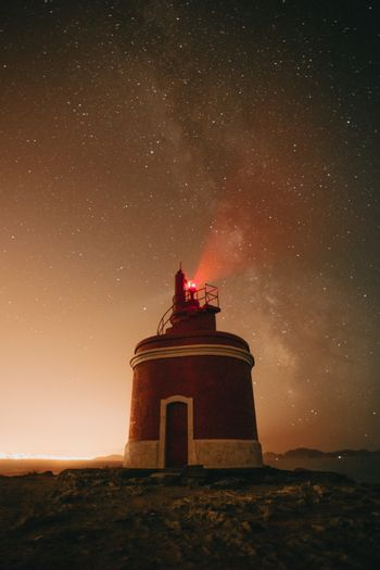 An horizontal shot of a lighthouse during the night with the milky way behind it