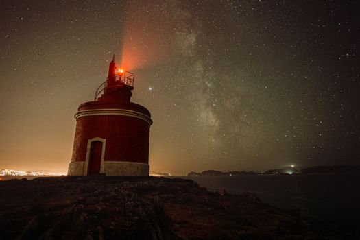 An horizontal shot of a lighthouse during the night with the sky with a lot of stars