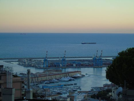Genoa, Italy – August 2020: Aerial view of shipping and container terminal, stacked containers and loading dock side cranes in the port of Genoa, Magazzini del cotone and Porto Antico, sea