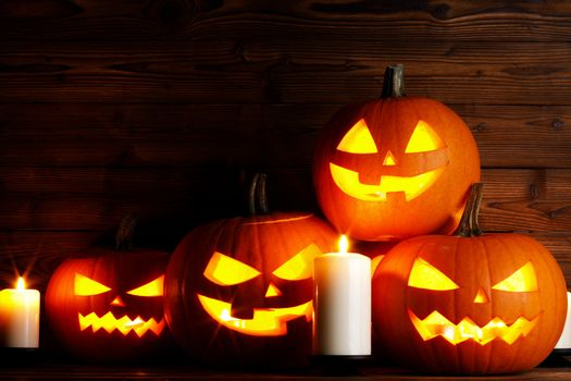 Many Halloween pumpkins head jack o lantern and candles on wooden table background
