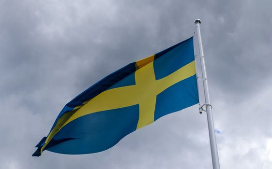 Sweden flag at a flagpole moving slowly in the wind against the