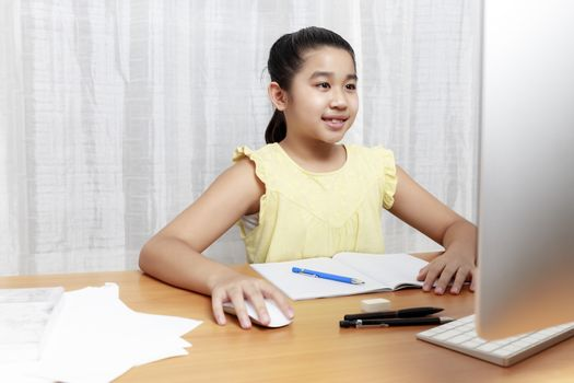 Asian young little girl using pencil to do homework by herself. Student kid writing  homework book. Girl use computer to study at home. Education homeschool  concept.