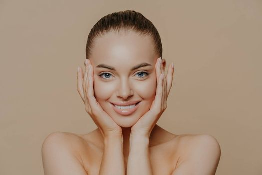 Skin care and beauty concept. Headshot of beautiful cheerful woman touches face gently, has perfect smile, healthy skin after cleaning or applying facial mask, isolated over beige background
