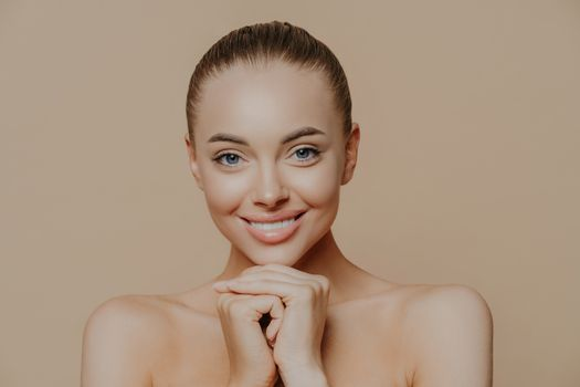 Close up shot of adult woman with fresh daily makeup, smiles toothily and keeps hands under chin, stands half naked indoor, feels refreshed after cosmetic procedures. Beauty and face care concept