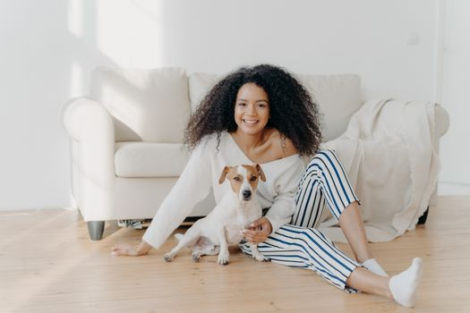 Relaxed young African American woman sits on floor in empty room near sofa with pedigree dog, enjoys sweet moment at home, move in new apartment to live. Lady rests with puppy in living room