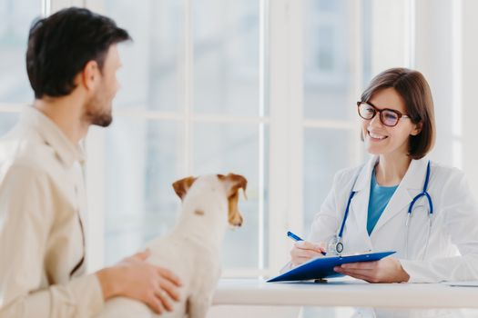 Man brings his pet fot vet examination in clinic, tells symptoms of ill dog. Happy woman veteranian writes down necessary prescription in clipboard for jack russell terrier after careful checkup