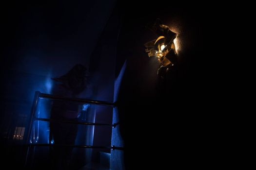 Horror concept. Scary mask with light on the wall inside dark room. Selective focus
