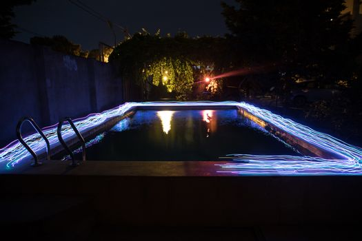 Pool at night - vacation background. Colorful light decoration. Freezelight