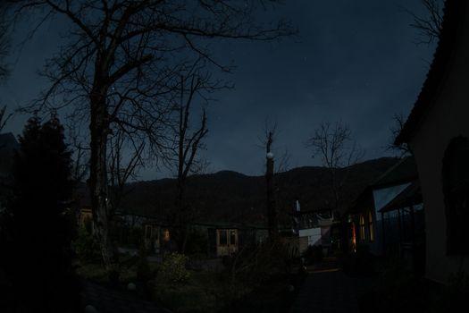 Full moon over quiet village at night. Beautiful night landscape of mountain village under the moonlight. Azerbaijan nature. Long exposure shot