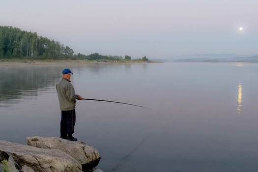 a fisherman catches fish early in the morning on the lake moon is shining in the sky