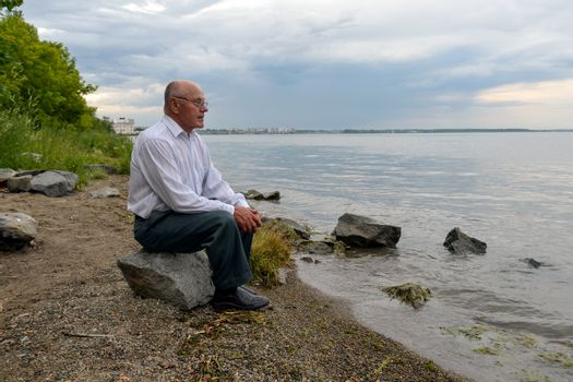 a lonely elderly man sits on a rock near the lake and looks into the distance