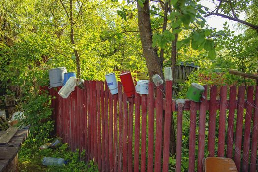 watering can is hanging on the fence