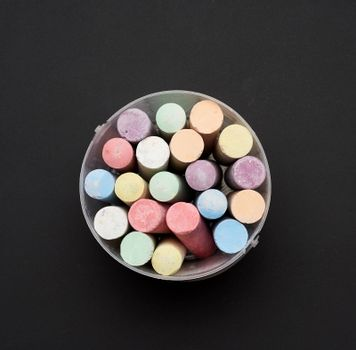 multicolored chalk in a plastic bucket on a black background, top view