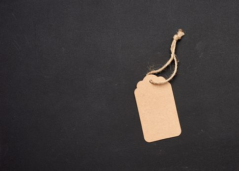 empty paper brown rectangular price tag on a rope on a black background, copy space
