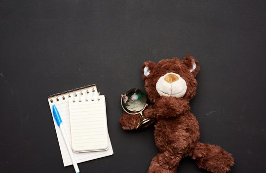 stack of notebooks with blank white sheets and a brown teddy bear holding a glass globe on a black chalk board background, back to school