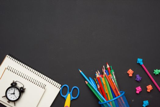 colorful wooden pencils, scissors, notepads on a blank black chalk board, school stationery, copy space, back to school
