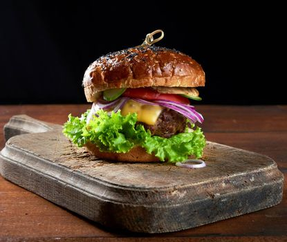 delicious burgers with fried beef cutlet, tomato, lettuce and onions, crispy white wheat flour bun with sesame seeds. Fast food on a wooden board, top view