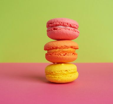 stack of baked macarons on pink green background, delicious dessert made from almond flour, close up
