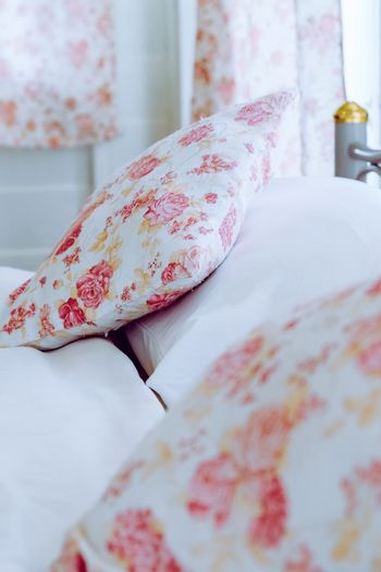 Bright bedroom interior with flower pattern pillows on bed