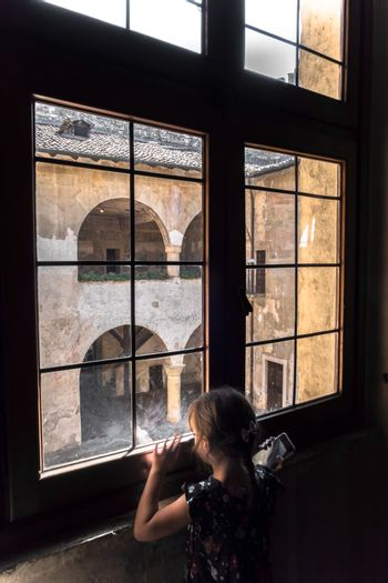 A little girl of 5 years with brown hair gathered in a braid looks through an old window in a castle.The little girl holds a black cell phone in her hand. Outside the window an ancient courtyard with large arches.