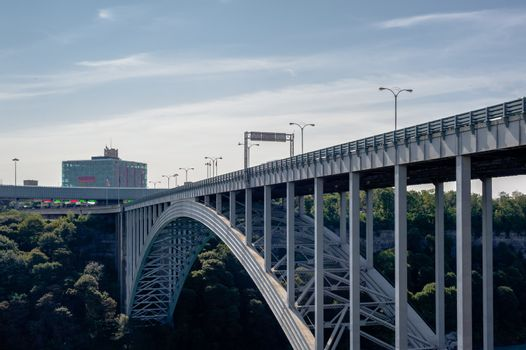 NIAGARA FALLS, CANADA - AUGUST 27, 2017: The Rainbow Bridge, viewed from the Canadian side of the Niagara River gorge, allows cars and pedestrians to cross the border between Canada and the United States.