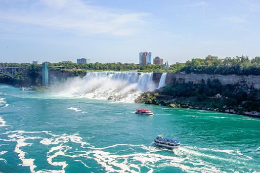 NIAGARA FALLS, CANADA - AUGUST 27, 2017: Tour boats full of passengers in colored raincoats visit the waterfalls.