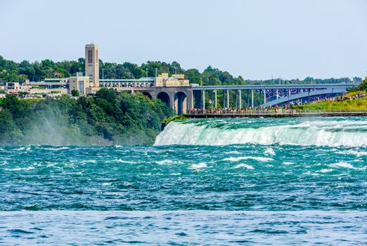 NIAGARA FALLS, CANADA - AUGUST 27, 2017: Tourists view the Horseshoe Falls from a platform on the American side, with bridges and the Canadian side of the border crossing in the background.