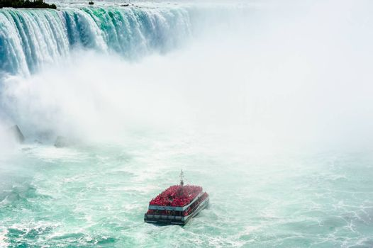 NIAGARA FALLS, CANADA - AUGUST 27, 2017: A tour boat full of passengers in red raincoats gets close to the Horseshoe Falls.