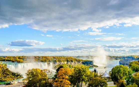 NIAGARA FALLS, CANADA - OCTOBER 26, 2017: A tour boat in the distance heads for the Horseshoe Falls on a sunny afternoon in autumn.
