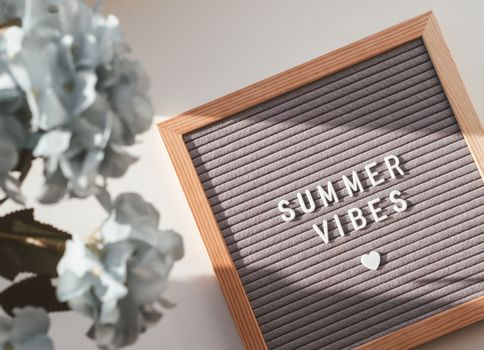Letter board with words SUMMER VIBES and heart. Top view on flat