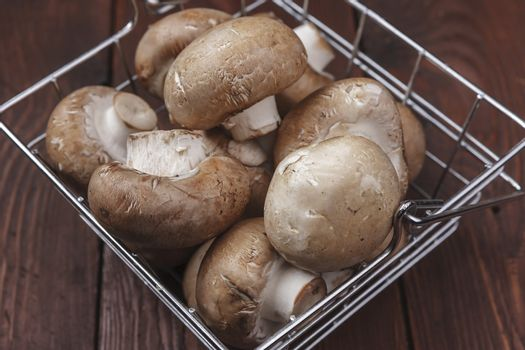 A close up of a metal wire basket full of fresh mushrooms.