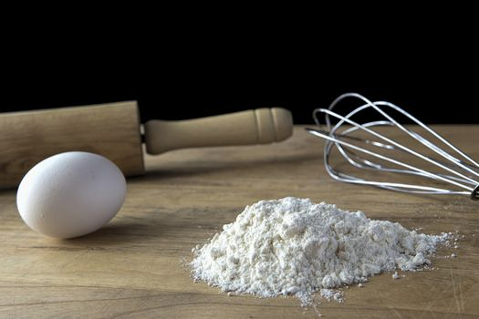 A concept photo of flour, eggs, a whisk and rolling pin.