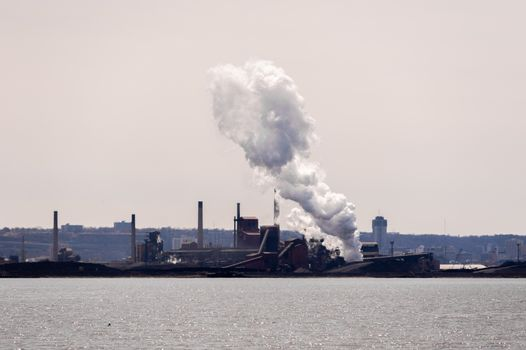 HAMILTON, ONTARIO, CANADA - APRIL 21, 2018: A large plume of steam drifting east is released at a steel plant on the shore of Hamilton Harbour.