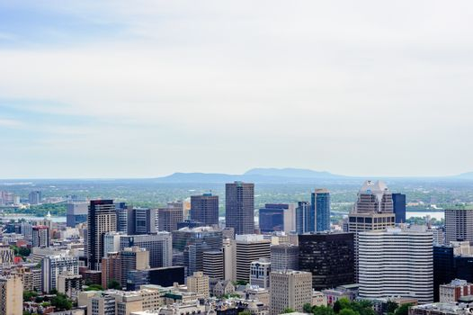 MONTREAL, CANADA - JUNE 16, 2018: Part of the downtown and mountains on the horizon can be seen looking east from Mount Royal.