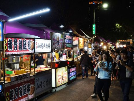 KAOHSIUNG, TAIWAN -- MARCH 2, 2018: Visitors flock to a night market with a large variety of food stalls.