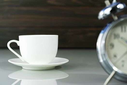 White coffee cup and alarm clock on table