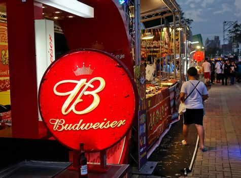 KAOHSIUNG, TAIWAN -- MARCH 2, 2018: An outdoor vendor at a night market sells grilled meat and Budweiser beer.