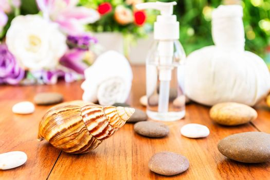 Spa concept,Snail and Bottle collagen or serum oil, Thai Spa massage setting with bottle with essential oil and thai herbal compress balls