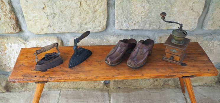 wo old rusty antique iron with wooden handle, hand coffee grinder and leather clogs on old wooden bench with sandstone wall background